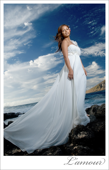 Bride in flowing destination wedding dress stands by the ocean in Hawaii