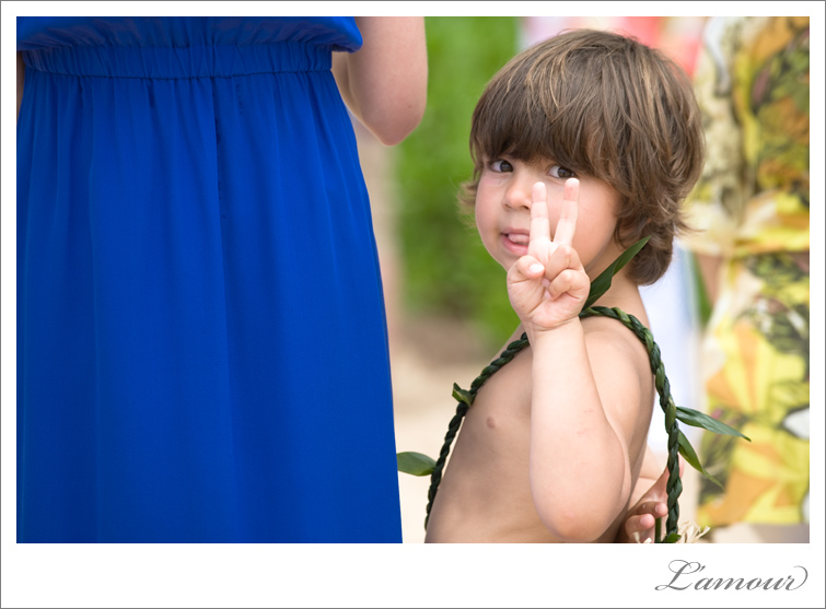 Hawaii wedding ringbearer in lei gives  the peace sign to photographers