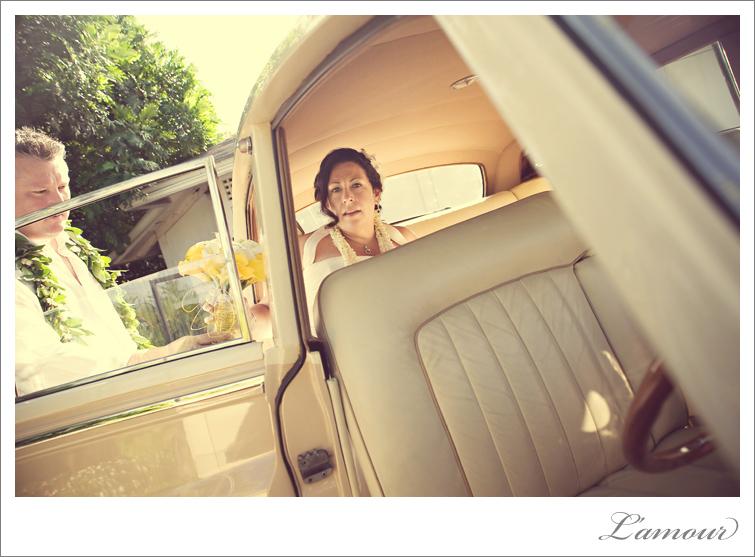 Hawaii Destination Wedding couple drive away in vintage car Rolls Royce