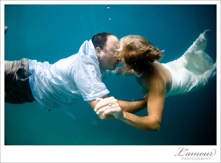 And groom kiss during their underwater trash the dress photo session