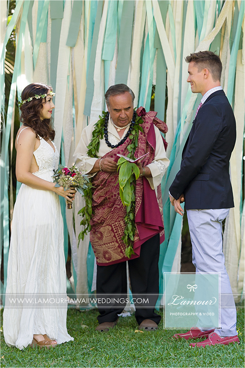 Wedding ceremony with floral headpiece haku with ribbon backdrop in hawaii