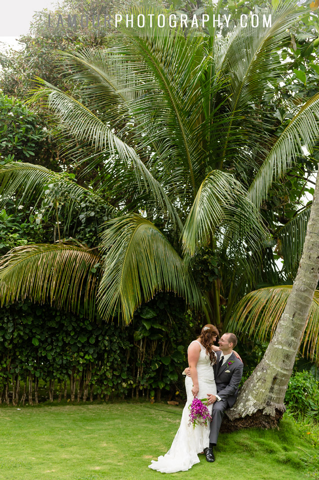 Hawaii destination wedding couple sitting on a palm tree at their reception on Oahu