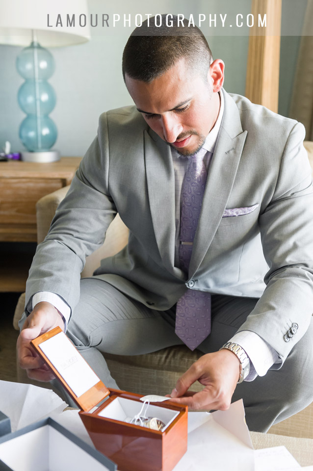Destination wedding in Hawaii groom in grey suit with lavender tie opening up a gift on his wedding day on Oahu