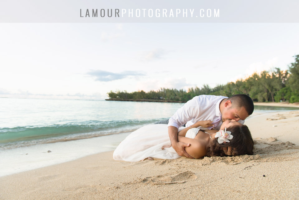 bride and groom share kiss on sand after hawaii wedding at turtle bay resort on pahu