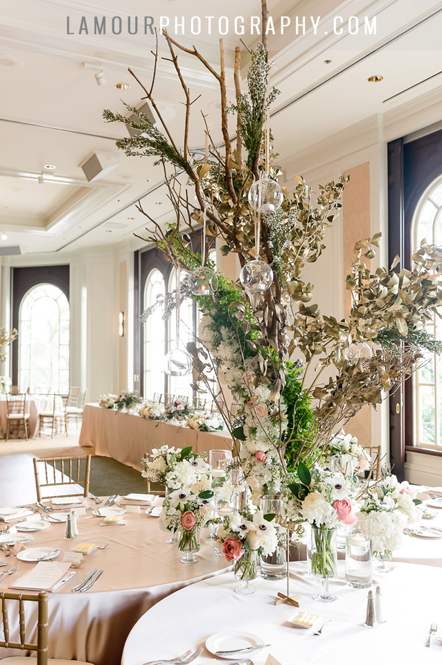 tall wedding centerpiece with hanging glass tea lights and blush pink and gold tables at Moana Surfrider in Hawaii