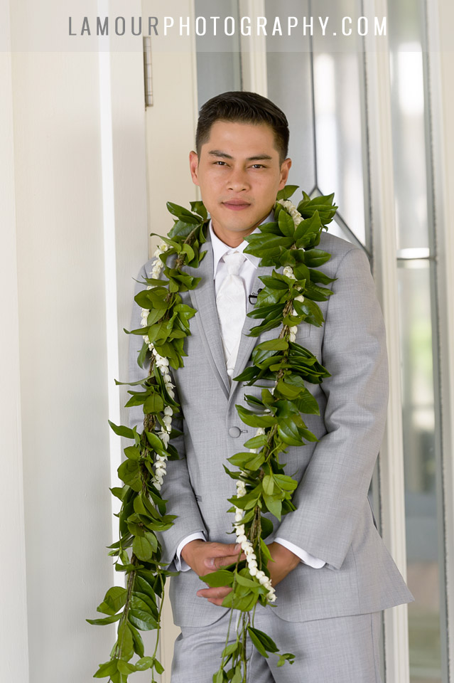 groom wears grey suit and lei at hawaii destination wedding