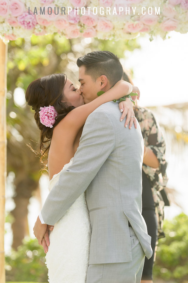 bride and groom share first kiss at hawaii wedding at venue turtle bay resort oahu