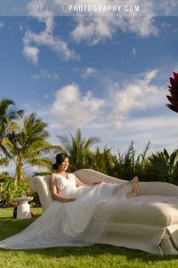 Bride lounging on chaise chair for reception in hawaii wedding