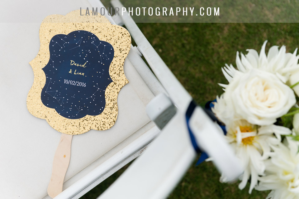 Destination wedding in hawaii had fans for guests during outdoor wedding ceremony with glitter gold outline, navy blue with stars and constellations.