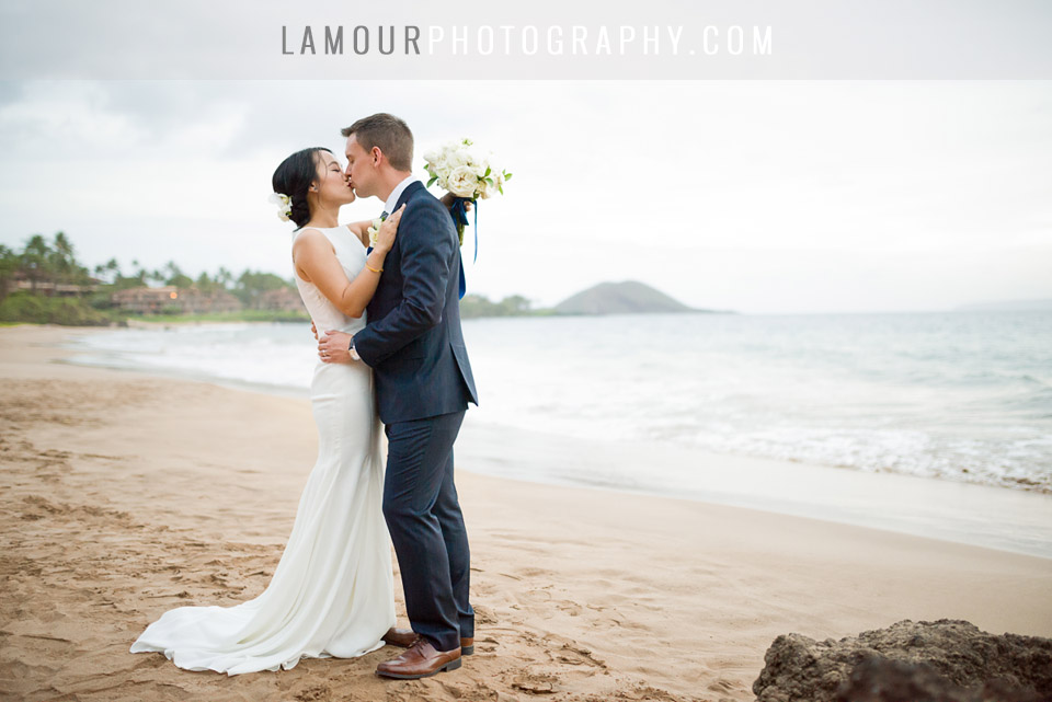 Hawaii wedding bride and groom kiss on the beach in Maui during their portrait session