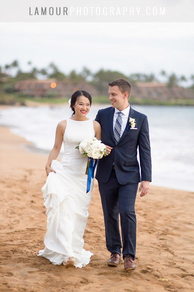 Bride and groom walk along the beach in Maui after their wedding ceremony while taking photos with the photo and video team from L'Amour