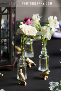 Small vases decorate a black, purple and gold wedding reception table in Hawaii