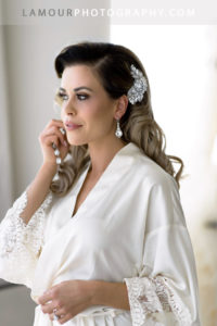 Bride in silk robe puts on earrings before putting on her dress for her Honolulu Wedding