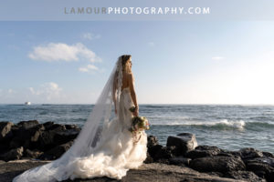 Bride in Hawaii wears strapless lace dress with sweetheart neckline and mermaid train along with a a long lace trim veil for her Wedding in Hawaii
