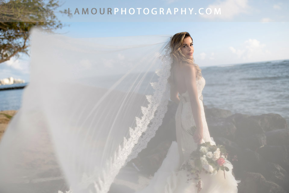 Long flowing, lace trim veil on bride for her destination wedding in hawaii on the island of oahu photographed by the team at L'amour