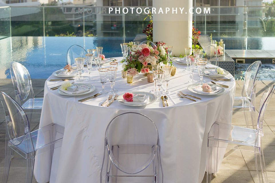 Oahu wedding reception at a hotel in Honolulu with clean white table cloth and clear oval back chairs with large floral centerpiece and gold decor accents