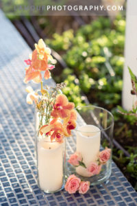 Hawaii wedding reception flowers in Oahu with candles, orchids and roses in glass vases