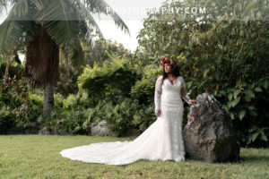 Bride in long lace wedding dress with long sleeves and deep cut poses for wedding photography