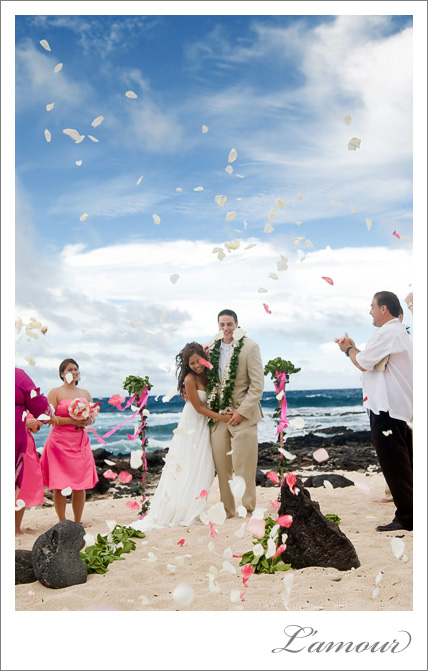 Hawaii Destination Wedding couple getting showered with rose petals on the beach