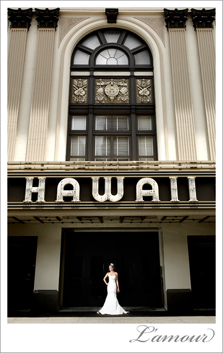 Bride in classic wedding dress stands in front of Hawaii Theatre