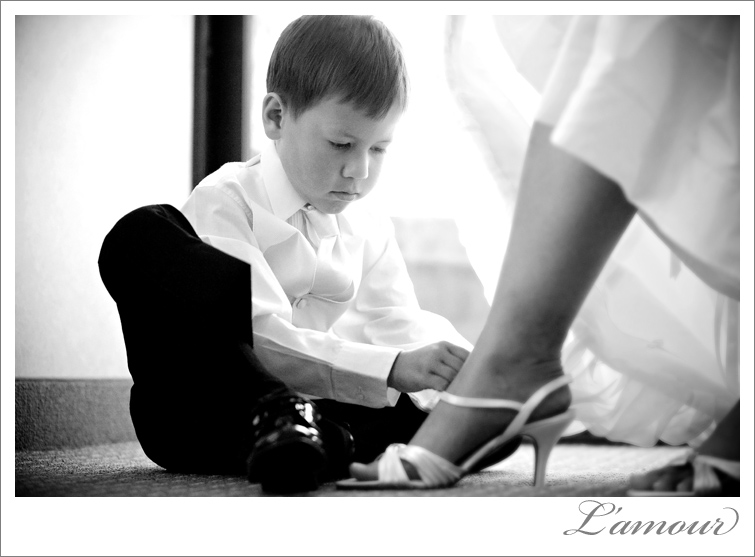 Ringbearer helps bride put on her wedding shoes