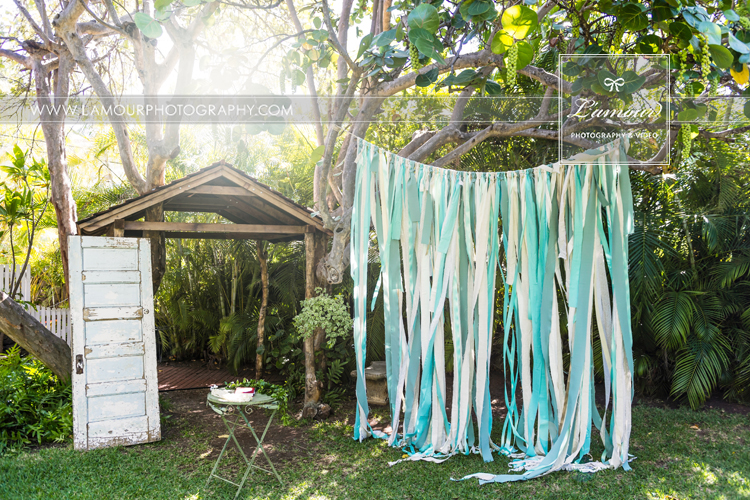 Bayer Estate wedding in Hawaii ceremony with blue and teal ribbon backdrop and antique door decor