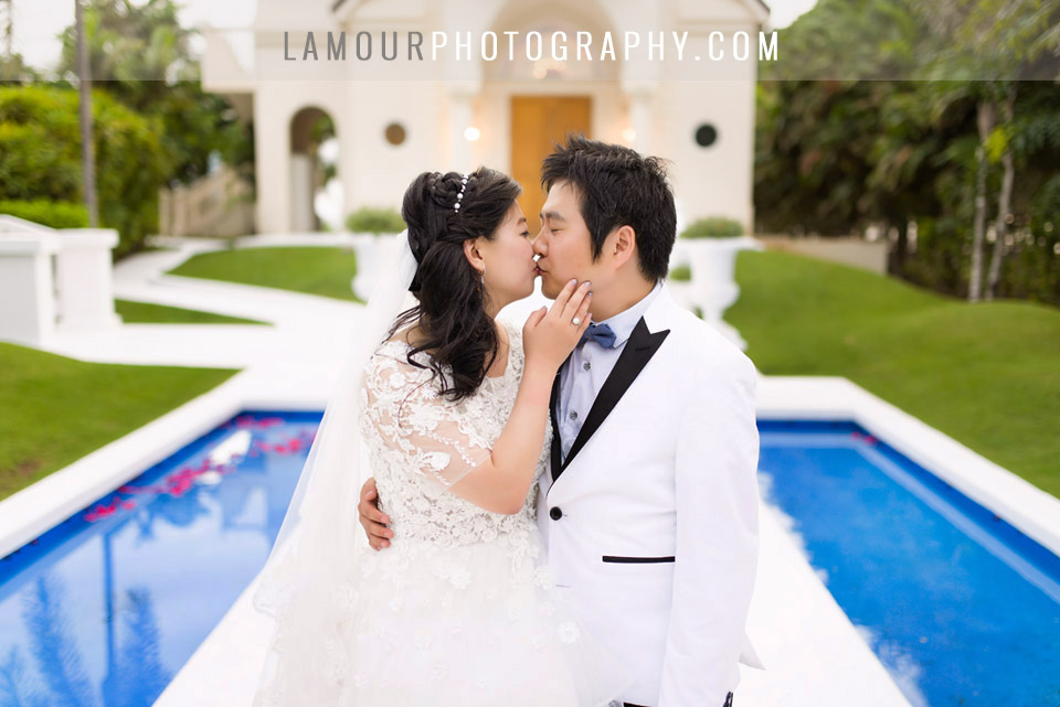 Destination wedding couple kiss outside crystal chapel on Oahu at Koolina
