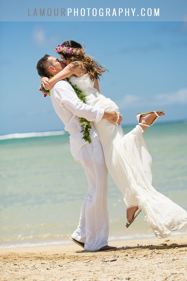 Destination bride and groom from Poland share a kiss with the beach and ocean behind in Hawaii
