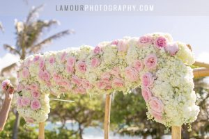 wedding ceremony arch with white and light pink flowers bamboo