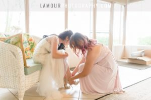 bride gets wedding shoes on in wedding photography