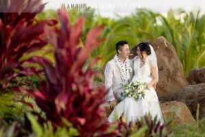 Hawaii bride and groom sit on lava rocks during wedding photography session and video in maui