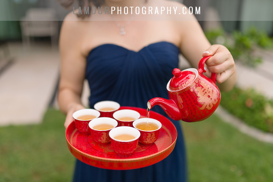 red themed wedding tea ceremony performed by bridesmaid in navy blue strapless dress