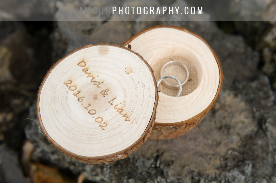 Destination wedding ring box made of piece of wood left raw and engraved with names and date