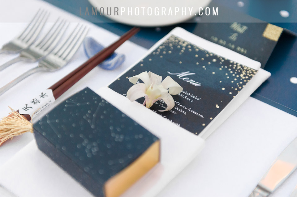 Hawaii wedding reception with navy blue and gold color scheme. Gold stars and constellations adorn the dinner menu, place card, and wedding favor box