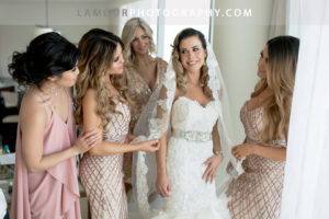 Bridesmaids in blush and pink color dresses help the destination wedding bride get dressed before the wedding ceremony