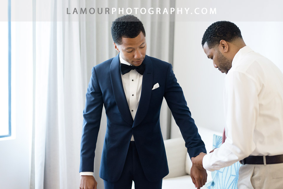 Groom in fitted navy blue suit and black velvet bowtie gets ready for wedding in Hawaii