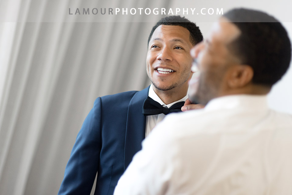 Groomsman helps groom get dressed in his navy blue suit for wedding ceremony on Oahu
