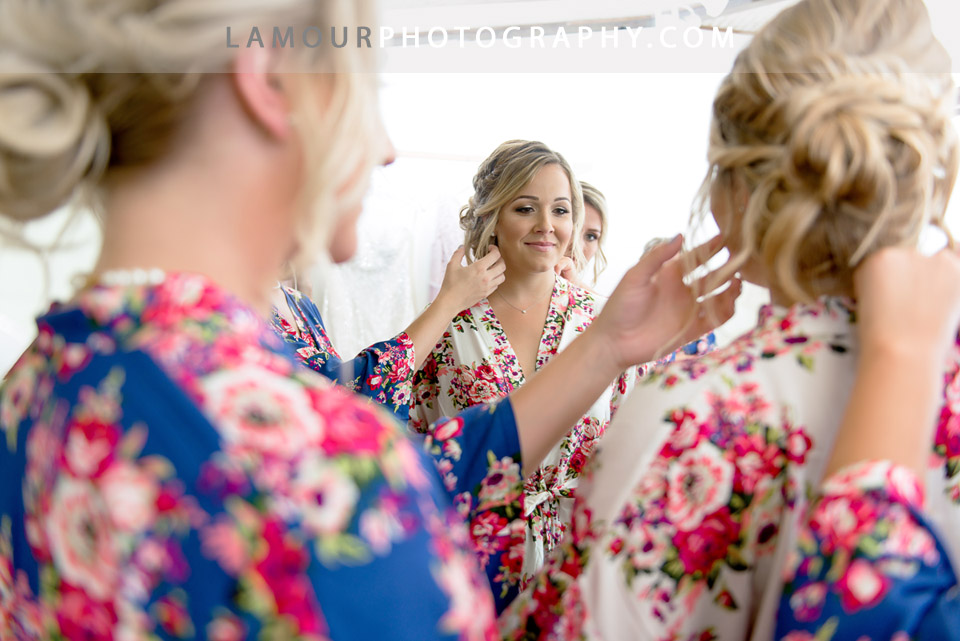 Bride and bridesmaids in coordinating floral robes get ready in hair and makeup on oahu