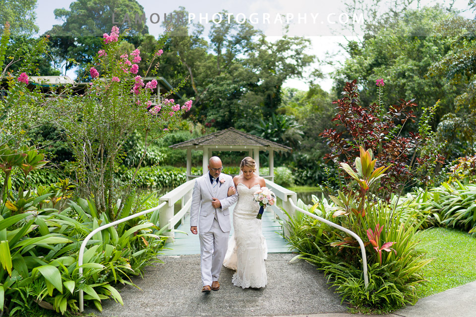 Bride walks down the aisle from the gazebo at Haiku Gardens in Kaneohe Hawaii