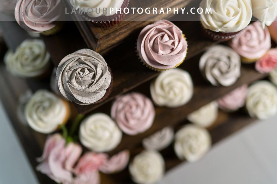 Buttercream frosted cupcakes in blush tones on a wood tiered cake stand for a Hawaii wedding
