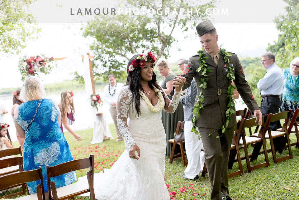 Hawaii Bride wears gorgeous long sleeve lace wedding dress with white flower lei and red flower crown haku