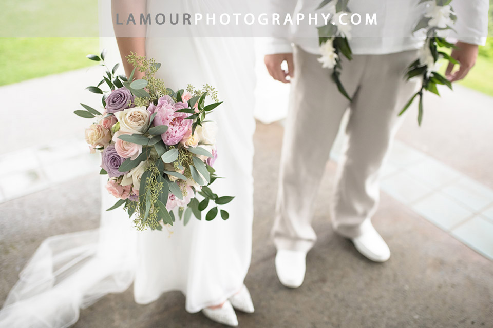 Bride and groom stand side by side for wedding photos and video showing the bride holding a flower bouquet with pink, white, and purple flowers for their Hawaii wedding at Turtle Bay Resort on Oahu